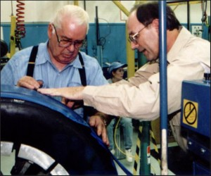 "Dr. McElroy and instructor Bill Gragg inspect ""Gum Cushion"" base before Pre-Cure tread is installed."